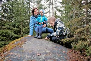 Här syns den. Neo Almsin, 13 år, visar slingorna på berghällen som är knappt synliga under påväxten av lav. Mamma Erika Nicklasson håller ett fast grepp om lillebror Måns, 3 år, för bakom dem stupar bergknallen flera meter.