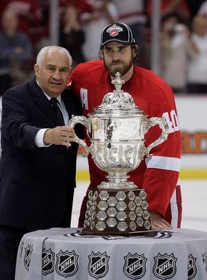 Jim Gregory, här i egenskap av vice president i NHL, med Clarence S. Campbell-bucklan som Inge aldrig fått vinna och i sällskap av Henrik Zetterberg. Gregory sköter för övrigt, vid 82 års ålder, fortfarande andra och tredje rundan under NHL-drafterna. Den första tar presidenten Gary Bettman alltid hand om. FOTO: TT