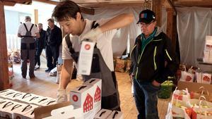 """Tapio Hurtta, till höger, fick lite rabatt på sitt köp av 54 kartonger äppelmust. """"Jag ska ge bort en hel del, och byta mot grannens mangold"""", säger han."""