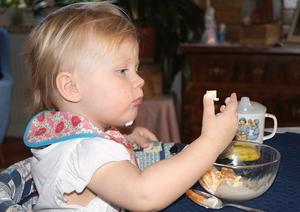 Ellen fick glass och clementinklyftor. Hon tittar på glassen på fingret och tycks tänka