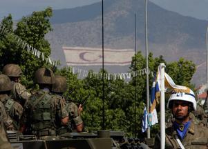 Cypern så väl som Nicosia är splittrat sedan 1974. Bilden är från 2008 på Cyperns självständighetsdag där ett gäng militärer syns framför den turkisk-cypriotiska flaggan. Foto: AP Photo/Petros Karadjias