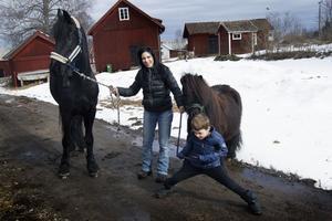 Jennifer Nilsson med frieserhästen Olle och Alexander Nilsson med shetlandsponnyn Blixten. De rider ofta ut tillsammans och på sommaren kan de också ses körande med vagn med Blixten framför.