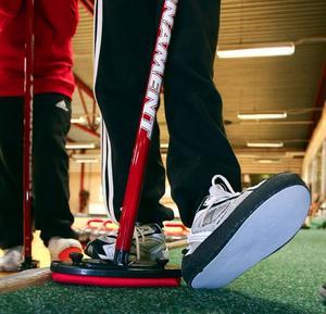 På den ena skon drar man på en glidsula för att man ska kunna glida med curlingstenen innan man släpper den.