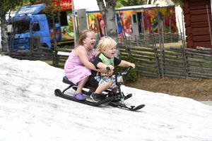 Elin och Kimi Sova åker pulka på svalkande snö två dagar efter skidtävlingen, något som lockar trots att barnen har ett eget tivoli i bakgrunden.