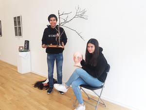 Elvis Merio visar sitt konstverk och Magda Oxhagen Nicolaides håller i en skulptur som Tuva Edfors har gjort. Foto: Maria Oscarsson Marle