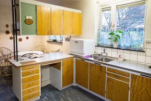 Köket med sina platsbyggda skåp med skåpsluckor i ek håller än.