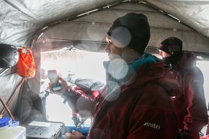I fukten i tältet vid baslägret nära Köldhålet tittade expeditionsledaren Dmitri Gorski på sin mobil och bilder tagna av Irena Stangierska.