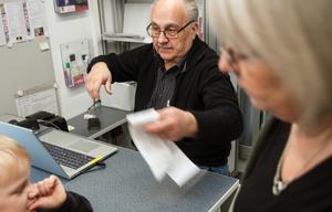 Bengt Strömberg tar emot och avregistrerar återlämnade böcker. Biblioteksassistenten Carina Bäcklin hjälper låntagarna att plocka fram