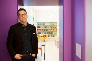 Bibliotekschef Johan Anderung visar hur vägen mellan barn- och ungdomslitteratur öppnats upp i lokalen.