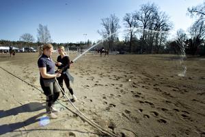 Lovisa Carlsson och Tilda Ersson vattnar inhoppningsbanan så den inte ska damma så väldigt.