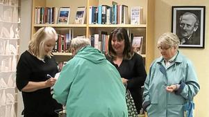 Doris Dahlin signerar böcker under en bild av Gustav Hedenvind-Eriksson. Foto: Ingrid Karlsson.