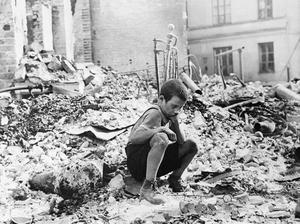 En polsk pojke sitter i ruinerna av sitt sönderbombade hus. Foto: Julien Bryan