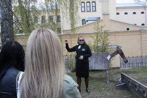 Margit Söderström berättar för eleverna om trähästen och stupstocken.