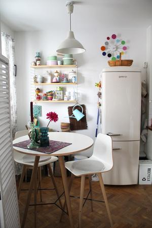 Det snygga kylskåpet fanns här när de köpte lägenheten. Den vita vikväggen döljer strykbrädan.
