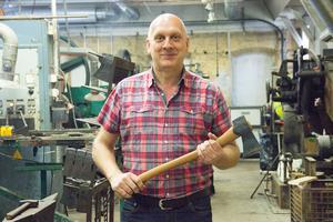 Platschefen Johan Ståhlberg visar en släggyxa, en av de fyra modeller som i dag tillverkas i yxfabriken i Storvik.