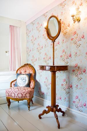 Det minsta gästrummet har en platsbyggd säng, rosiga tapeter och möblerat med en näpen Emma-fåtölj och ett stiligt spegelbord.