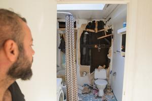 Jony Abdulmasih tittar in i badrummet där brandmännen har brutit upp ena väggen under släckningsarbetet.