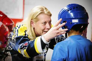 Catharina Elmsäter-Svärd har varit engagerad i SSK på olika sätt i flera år, de senaste fyra åren som ordförande. Här hjälper hon ett barn med hjälmar i ett integrationsprojektet inom SSK.