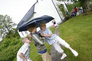 Regnet vill inte ge med sig. Samuel Grönlund, Isak Martelleur och Filip Geholm tränger in sig under samma paraply.
