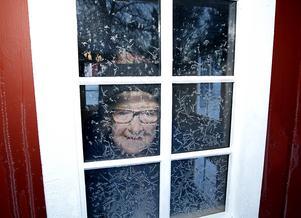 Stina tittar ut genom det frostiga fönstret i lekstugan.