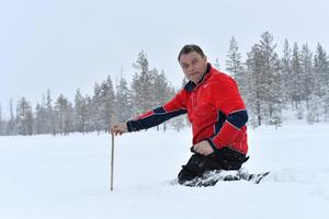 John Liif mäter snö vid Smågan, men redan vid åtta decimeter sätter den hårt packade snön stopp för tumstocken. De 160 cm höga ledkryssen sticker bara upp med någon decimeter.