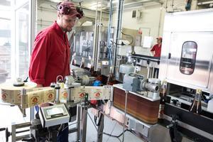 Jacob Tillman övervakar den helautomatiska tappningslinjen. Där fylls 5-6000 flaskor i timmen.  Bären färskpressas vilket ger klara råsafter.