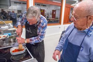 Kjell-Åke Norgren mosar tomaterna under Gerhard Hauptigs överinseende.