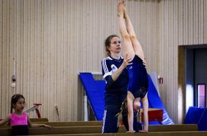 Nora Samuelsson övar handstående på bom med hjälp av Jessica Wallskog Svensk.