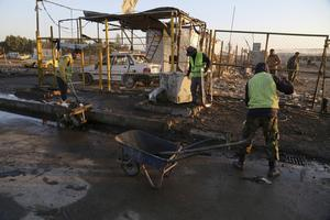 Gaturarbetare städar upp efter en av bilbomberna som exploderat i Bagdad de senaste dagarna.