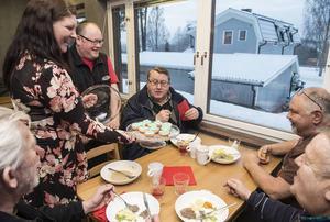 Kaféägaren Irene Gaunt bjuder herrarna Pelle Nordlander och Arne Johansson på cup cakes.