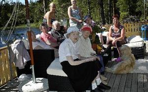 Längst fram i bild syns Solveig Hammarling och Märta Olsson. Bakom i soffan sitter Gully Pollack, Elsa Bertils och Erik Ahlbäck. På räcket sitter undersköterska Annelie Netzell och Natalie Jakobsson, vårdbiträde för sommaren. I blå hatt syns Erik Aggerbor
