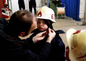 Markus Hägglund får hjälp av pappa Robert att få på brandmanshjälmen.