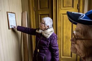 Tora Larsson och Doris Berglund läser bänkläggningslängden; sin plats i kapellet fick man efter yrke och titel.