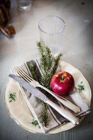 En grankvist och ett rött äpple ger dukningen den rätta julstämningen.