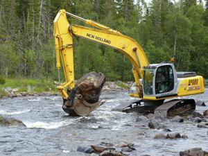 Nu läggs de stora stenblock som flottningsföretagen tidigare rensade ur Storån ut i vattnet igen. Stefan Ellingsson spakar grävmaskinen.
