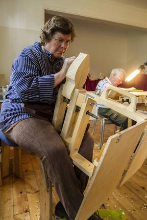 Trudy Calÿn täljer sittandes i arbetsbänken. Bakom henne sitter nybörjaren Bernt Larsson och täljer en välkomstskylt.