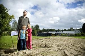 Jan Lötberg med barnen Alvin och Nora på den tomma yta där lekparken tidigare låg.
