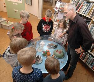 Leif Nordlöf visar barn från Celsiusskolans klass 1 runt på utställningen Kråkfötter på Edsbyns bibliotek.