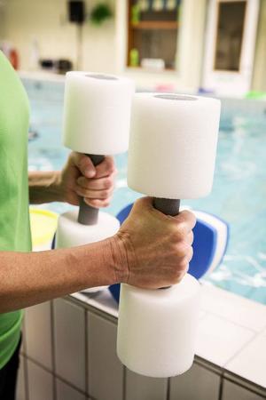 Anki Forsberg menar att vattenträning är en skonsam och bra träningsform. Här visar hon ett par hantlar som ger ökat motstånd i vattnet.