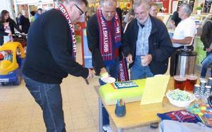 Lars Bergkvist och Pierre Jonsson, vinnarambassadör på Svenska spel skär upp tårta för att fira vinsten på lördasgens stryktips. Här är det Ingemar Karlsson som firar med en bit tårta. FOTO: ILSE VORNANEN