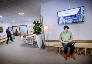 Simon Sköld är en av tre arbetsterapeuter på Karlslundsgården. Här provkör han den moderna övervakningstekniken via så kallade sensorgolv. På väggen bakom syns en av de många digitala skärmarna med aktuell information om Karlslundsgården.