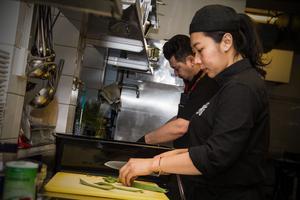 Köksbiträdet Tik Karlsson hjälper Özkan Ütük i köket med matlagningen.
