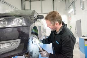Stefan Blom kontrollerar däcken på en bil.
