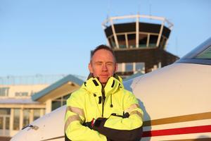 Per Nordahl, flygplatschef på Dala Airport, lutar sig mot en Hawker 400 XP. I bakgrunden syns flygledartornet.