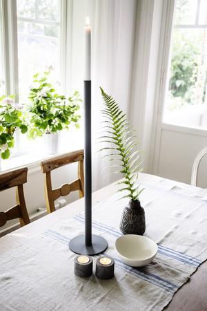 De enkla linjerna i ljusstakarna skapar en vacker kontrast till det lantliga köket.