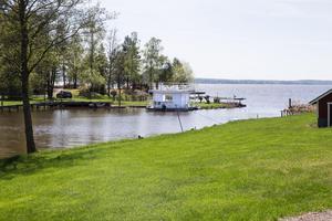 Husbåten ligger i en sommargrön idyll längs Mälaren i Västmanland.