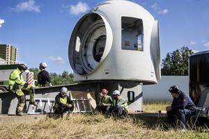 Huven hör hemma högst upp i vindkraftverket och det är där vingarna ska fästas. Personal från den tyska vindkraftstillverkaren Eno energy tar en paus i arbetet.