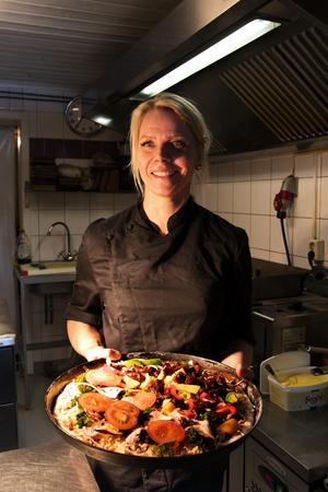 Elaine Asp stornjuter av att laga mat. Lunchpizzan med paprikor, bacon och Souvas (rökt reninnanlår) på väg in i ugnen för gräddning.