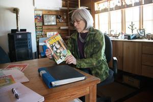 Ulla Mortimer kan tänka sig att bidra med seriealbum till Hälge-museet. Här bläddrar hon i en Hälge-tidning vid bordet i ateljén stora rum. I dag görs Hälge av serietecknare i Skåne, konstaterar hon.