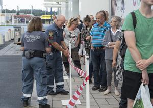Vakter fanns på plats för att hålla ordning på kön. Morgan Dahlsten sätter upp avspärrningsband för att styra människorna bort från trafiken.